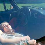 Woman resting in car.